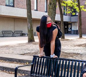 Three students talking keeping social distance and wearing masks