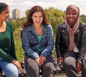 Group of female students sitting on a bench outside at Keele Campus, York University.