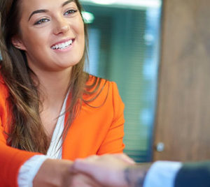 Female candidate shaking hands with a male supervisor during a job interview